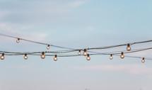string of lightbulbs and blue sky