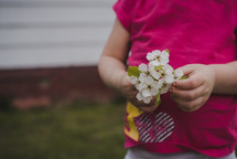 toddler girl holding picked flowers
