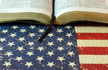 An open Bible on an American flag.