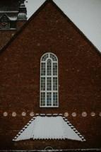 snow on a brick church roof