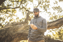 a man looking at his cellphone screen standing outdoors