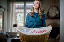 A smiling woman holding a basket of laundry.