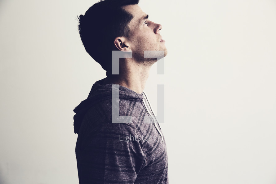 side profile of a man looking up.