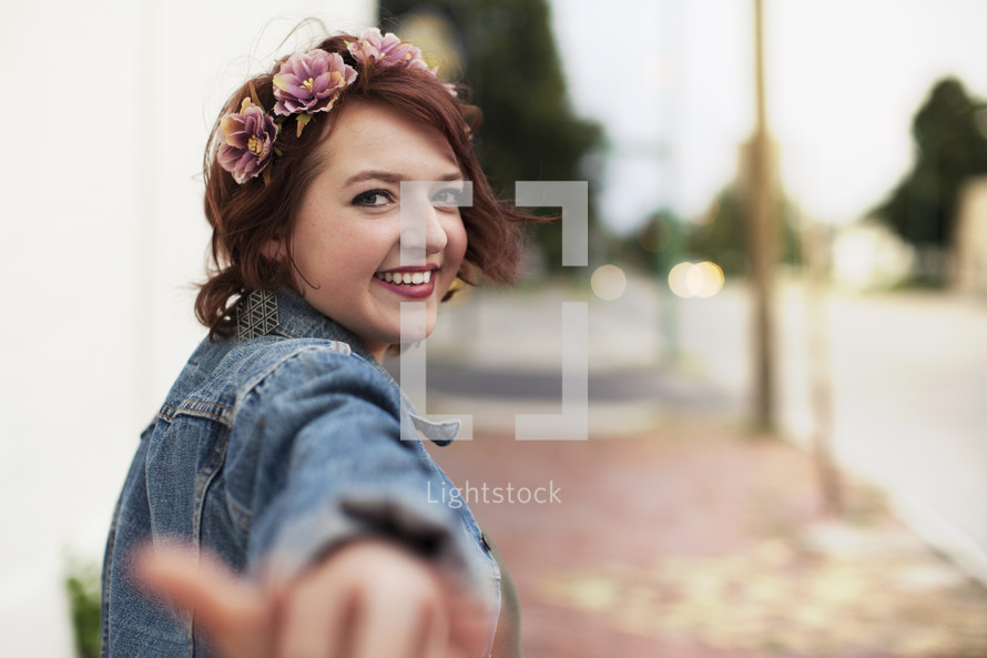 a young woman with outstretched hand, come this way