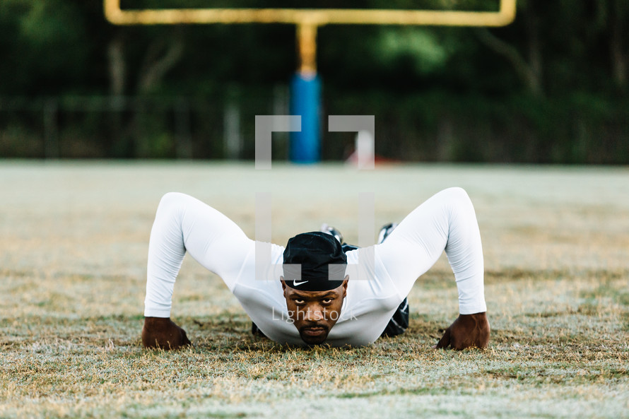 a man on a football field doing pushups