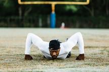 a man on a football field doing pushups
