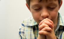 A boy folds his hands in prayer  with his eyes closed.
