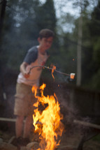 A boy roasting a marshmallow over a campfire.