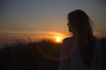 A woman facing the sunset.