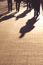 Shadows of people walking on a paved street.