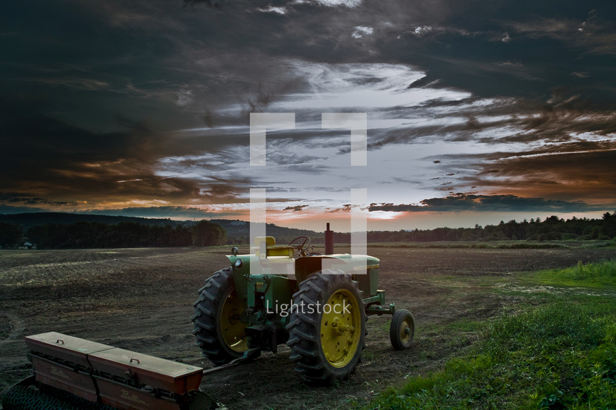 tractor in a field at sunset