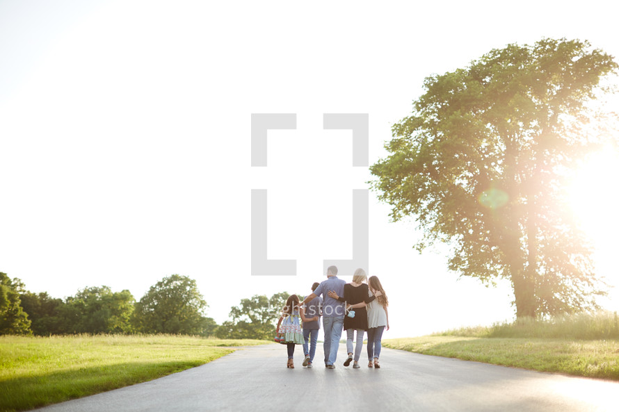 a family walking together with arms around each other down a rural road
