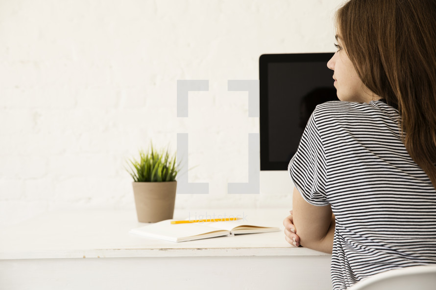 a teenage girl sitting at a desk working at a computer