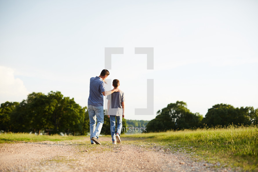 a father and son walking down a dirt road talking