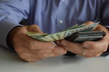 man holding his wallet and counting cash, debt, bills, paying, wealth, businessman