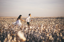 a couple holding hands running through a field of cotton