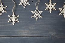 snowflake ornament border hanging on a wooden background.