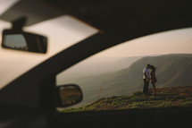 a couple holding hands on a mountaintop