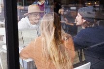 friends sitting in a window studying at a coffee shop