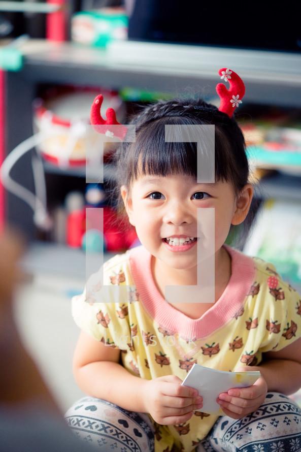 child wearing reindeer antlers
