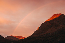 rainbow over mountain peaks