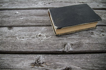 Old worn leather Bible cover on wood table