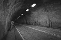 man walking in a highway tunnel