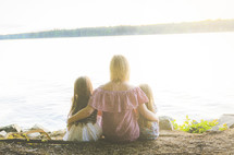 a mother and her daughters sitting at a lake shore