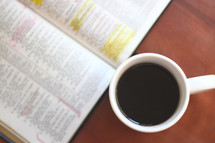 coffee mug and highlighted pages in a Bible