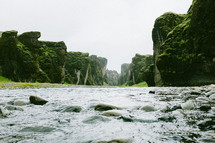 mossy rock cliffs and a stream