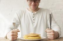 Man eager to eat his pancakes.