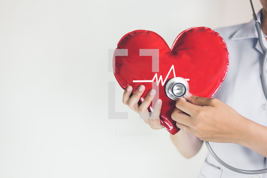 healthcare worker holding a heart and stethoscope