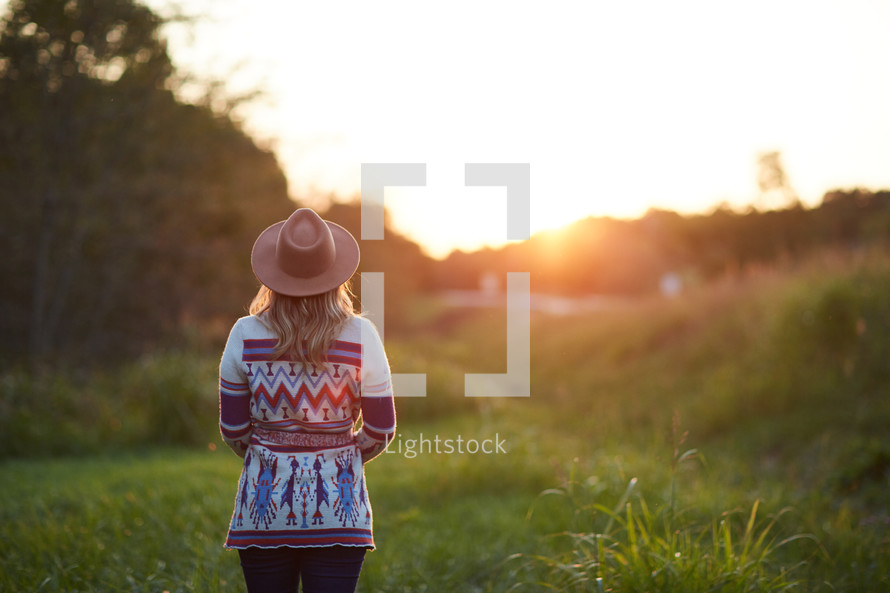 a woman in a sweater and hat standing in the middle of a field at sunset