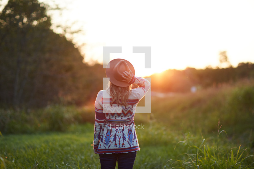 a woman in a sweater and a hat standing in the middle of a field at sunset