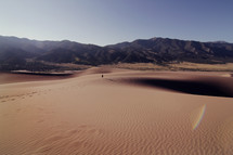 Person walking through sand in the desert, leaving a trail of footprints, with mountains in the background.