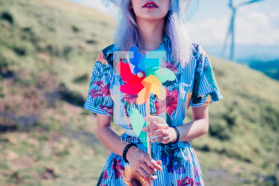 a woman holding pinwheels
