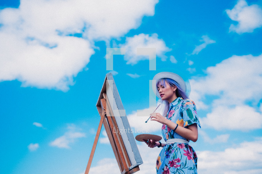 a woman painting outdoors
