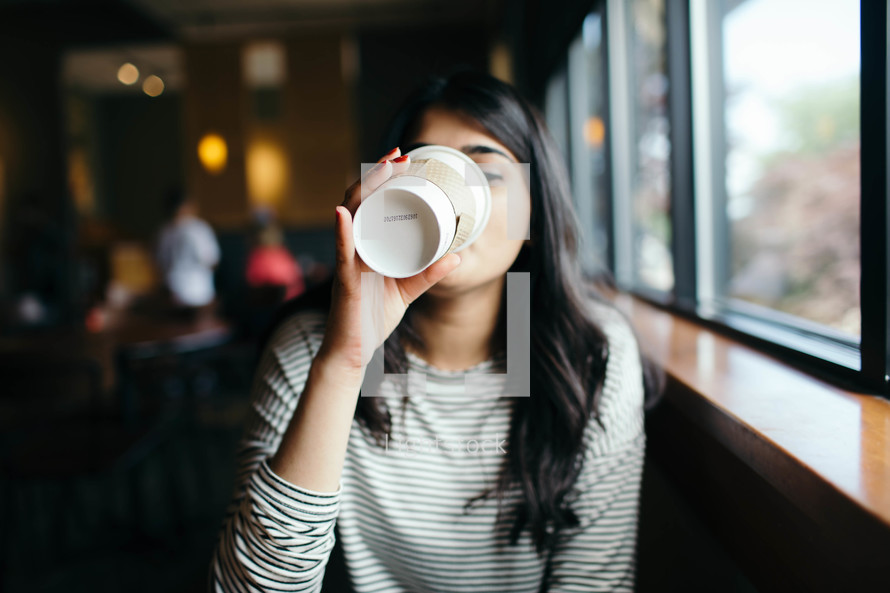 a young woman in a window seat of a coffee shop drinking coffee