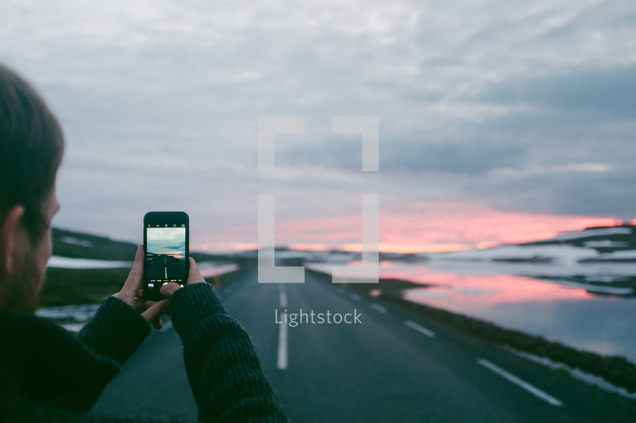 a man taking a picture with his cellphone of a rural highway at sunset