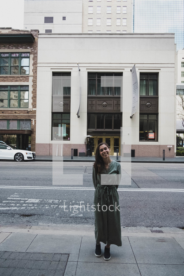 a woman standing on a sidewalk downtown
