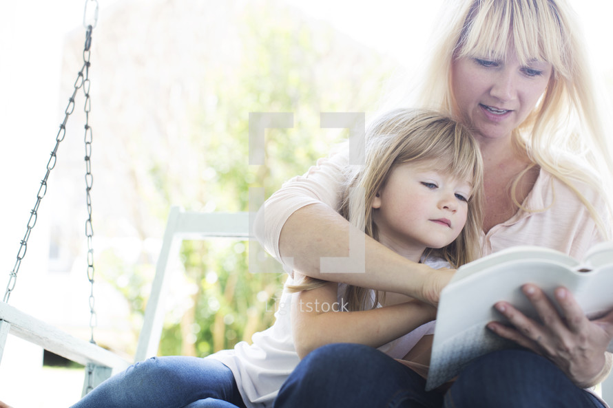 mother reading the Bible to her daughter.