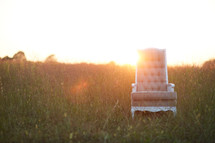 empty chair in a field of tall grass