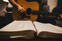 A man playing a guitar and an open Bible.