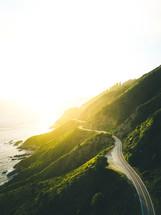road along a mountainous shoreline at dawn