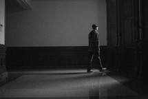 man walking in a hallway