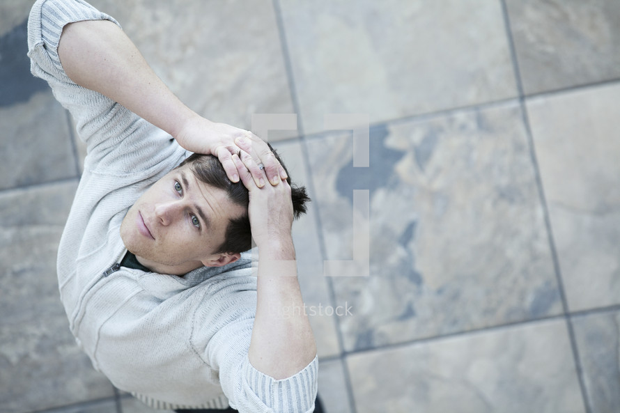 Aerial view of man standing on tiles with his hands on his head, looking up.