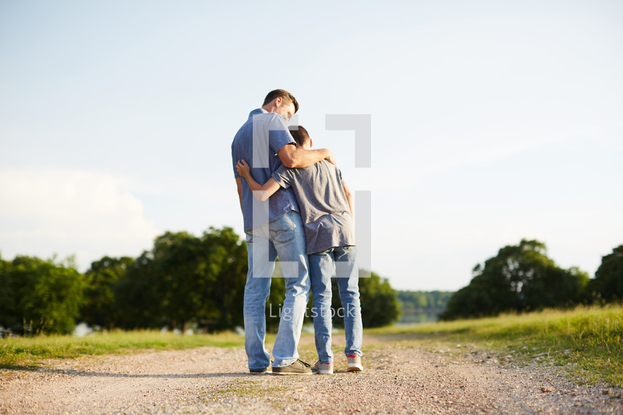 a father and son hugging standing on a dirt road