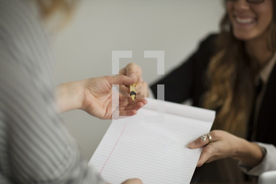 A smiling woman hands someone a blank pad and a pen.