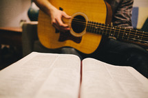 A man playing a guitar while looking at a Bible.