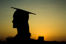 silhouette of a female graduate at sunset